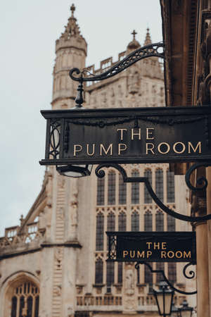 Bath, UK - October 04, 2020: View of the sign at the entrance to the Pump Room, a well-preserved Roman site for public bathing. Bath Cathedral on the background.