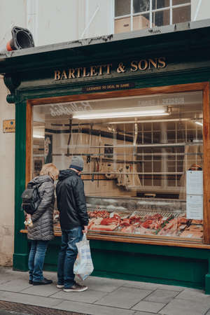 Bath, UK - October 04, 2020: Couple looking at the variety of meat in the window of Barlett & Sons butchery in Bath, the largest city in the county of Somerset, UK, named after its Roman-built baths. Sajtókép