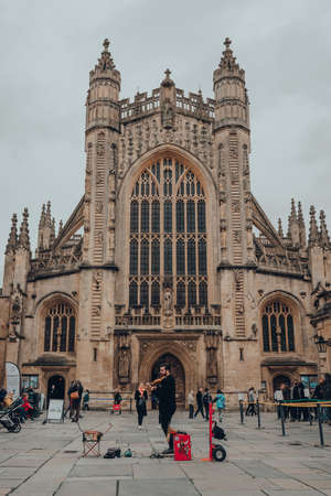 Bath, UK - October 04, 2020: Street performer playing violin in front of a cathedral in Bath, the largest city in the county of Somerset, England, known for and named after its Roman-built baths.