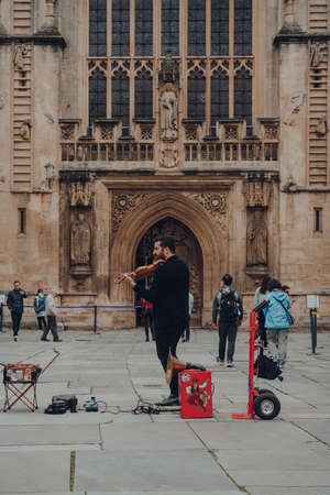Bath, UK - October 04, 2020: Street musician playing violin in front of a cathedral in Bath, the largest city in the county of Somerset, England, known for and named after its Roman-built baths.