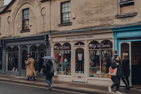 Bath, UK - October 04, 2020: Row of shops on a street in Bath, the largest city in the county of Somerset known for and named after its Roman-built baths, people walking past, motion blur.