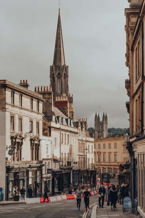 Bath, UK - October 04, 2020: People on Broad Street in Bath, the largest city in the county of Somerset known for and named after its Roman-built baths.