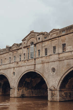 Bath, UK - October 04, 2020: View of Pulteney Bridge over River Avon, one of only four bridges in the world to have shops across its full span on both sides, Bath, Somerset, UK. Sajtókép