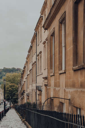 Street view of a row of old stone terraced houses on a street in Bath, Somerset, UK. Sajtókép