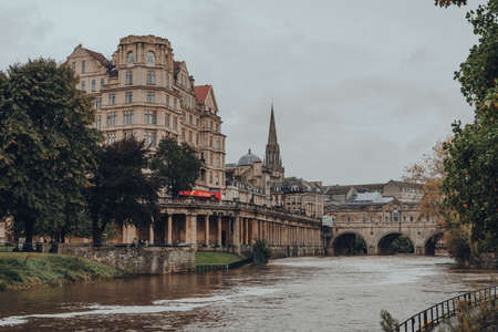 Bath, UK - October 04, 2020: View of Pulteney Bridge over River Avon, one of only four bridges in the world to have shops across its full span on both sides, Bath, Somerset, UK. Selective focus. Sajtókép