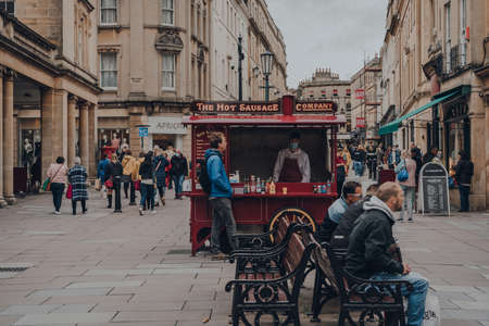 Bath, UK - October 04, 2020: Staff in face mask at Hot Sausage food cart on a street in Bath, the largest city in the county of Somerset, England, known for and named after its Roman-built baths.