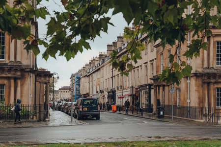 Bath, UK - October 04, 2020: View of Brock Street from under the tree on The Circus, a historic street of large townhouses in the city of Bath, Somerset, England.