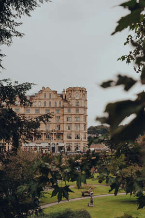 Bath, UK - October 04, 2020: View through the trees of buildings on Grand Parade in Bath, the largest city in the county of Somerset, England, known for and named after its Roman-built baths.
