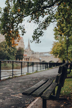 Empty bench on the bank of the river Avon in Bath, UK, the city on the background, selective focus. Stock fotó