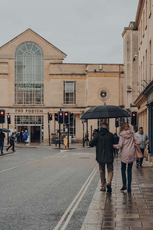 Bath, UK - October 04, 2020: Rear view of a senior couple walking on a street in Bath, the largest city in the county of Somerset known for and named after its Roman-built baths, on a rainy day.