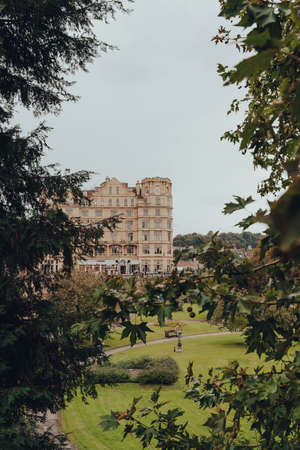 Bath, UK - October 04, 2020:View through the trees of Parade Gardens and buildings on Grand Parade in Bath, the largest city in the county of Somerset known for and named after its Roman-built baths. Sajtókép