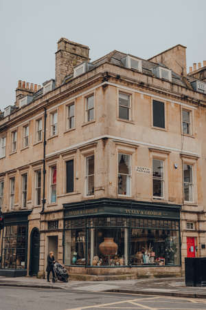 Bath, UK - October 04, 2020: Facade of closed Tully & George gift shop in Bath, the largest city in the county of Somerset known for and named after its Roman-built baths, woman walking past.
