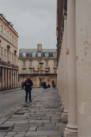 Bath, UK - October 04, 2020: Man in face mask using phone standing on Bath street in Bath, the largest city in the county of Somerset known for and named after its Roman-built baths. Selective focus