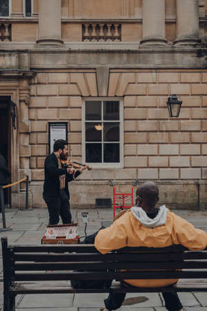 Bath, UK - October 04, 2020: Street musician playing violin on a street in Bath, a city in the county of Somerset known for and named after its Roman-built baths. Selective focus.