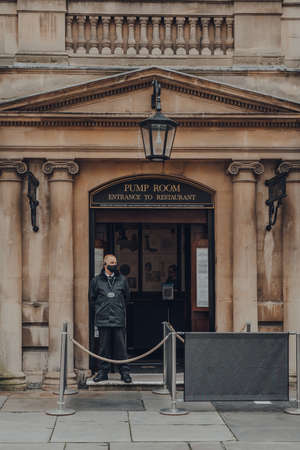 Bath, UK - October 04, 2020: Security guard in face mask standing at the entrance to the Pump Room Restaurant, a well-preserved Roman site for public bathing.