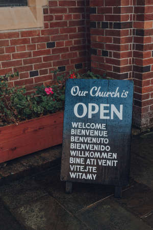 Rye, UK - October 10, 2020: Open sign outside St Anthony of Padua Church, a Roman Catholic Parish church in Rye, one of the best-preserved medieval towns in East Sussex, England.