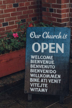 Rye, UK - October 10, 2020: Close up of open sign outside St Anthony of Padua Church, a Roman Catholic Parish church in Rye, one of the best-preserved medieval towns in East Sussex, England.
