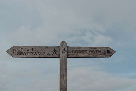 Direction signs along the coastal South West Coast Path route on Jurassic Coast World Heritage Site, Dorset, UK, against the sky.