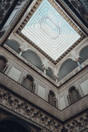 Seville, Spain - January 19, 2020: Low angle view of skylight in Dolls Courtyard of the Mudejar Palace in Alcazar of Seville, a royal palace built for the Christian king Peter of Castile.