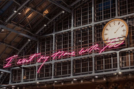 "London, UK - August 16, 2019:""I want my time with you"" glowing pink words installation by Tracey Emin within interior of St. Pancras, one of the largest railway stations in London and home to Eurostar"