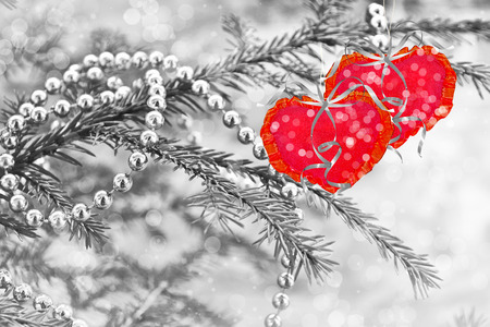 Snow-covered tree. Festive winter background. Two hearts. 免版税图像