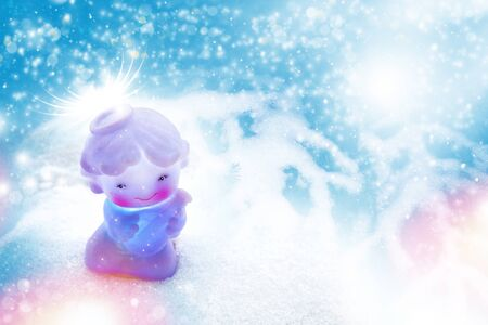 Greeting Christmas card. Little white angel in snowdrifts.