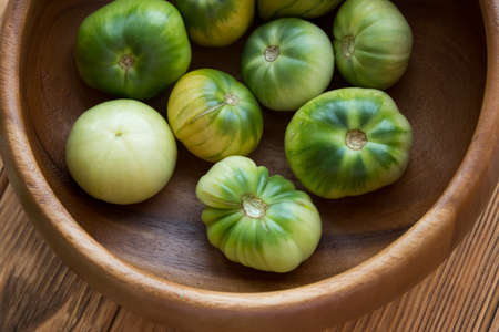 Green tomatoes on a wooden background. Tomato harvest Banque d'images