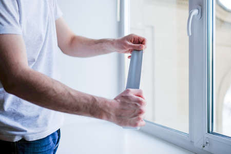 Worker putting sealing tape on window in house Stock Photo