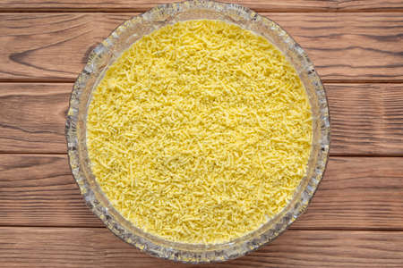 The process of cooking fish layered salad Mimosa. Laying grated egg yolk.