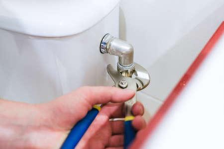 Sanitary worker performs repair of toilet bowl Stock Photo
