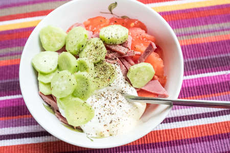 Salad of fresh cucumbers, tomatoes, beef, black pepper, sour cream, mayonnaise