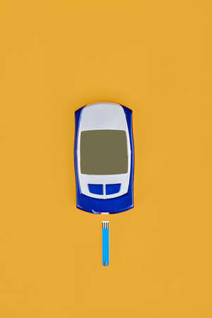 Blood Glucose Meter With Test Strip Isolated On yellow background with empty display
