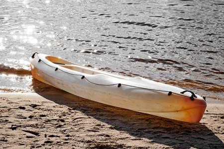Orange Kayak on the shore in sunlight