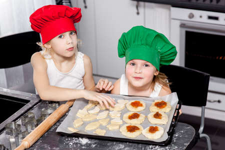 Two cheerful girls cook in colored caps prepare dough