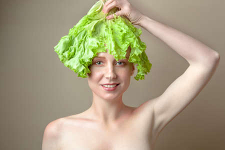 Sorprendido chica modelo con estilo de pelo de lechuga. Hermosa mujer joven feliz con verduras en su cabeza. Concepto de alimentos saludables, dieta, comida vegetariana. Concepto de dieta. Pérdida de peso. Comida vegana