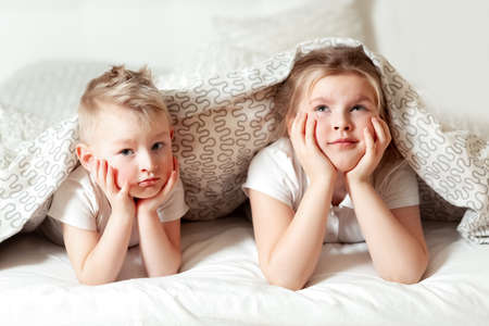 Portrait of cute siblings under blanket in bed