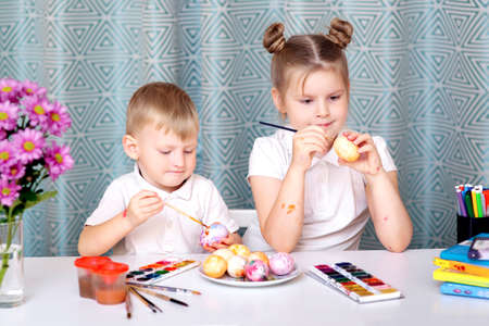 Smiling cute girl and her little brother painting one of eggs while both preparing for Easter holiday