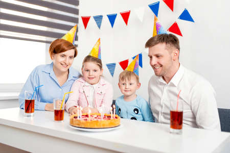 Happy family, mother, father, son, daughter celebrating a childrens birthday party with the cake. Emotions, joy
