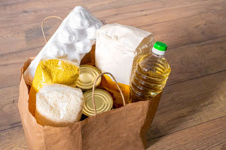 cereals, grains, oil, stew, porridge and canned food groceries in a craft bag for purchases .
