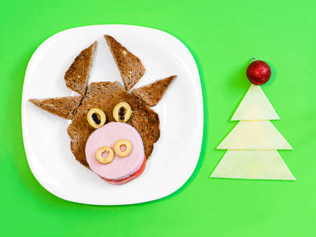 Funny a sandwich with edible symbol of 2021 bull cow made from toaster bread, sausage and cheese, Breakfast idea for kids. New Year Christmas food top view. Food art. Stock Photo