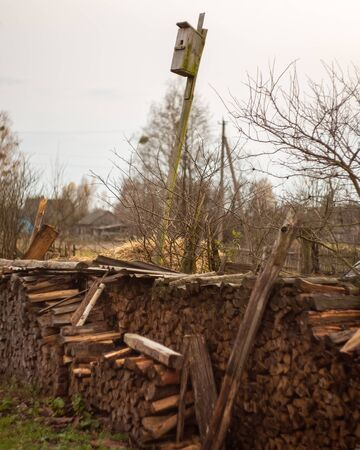 Old birdhouse in the background of the sky and firewood in two rows.