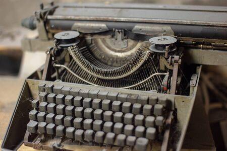 Vieille machine à écrire antique en gros plan dans la poussière.