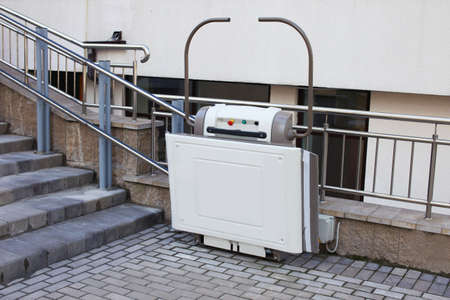 Stair lift for the disabled. Lift on the street near the stairs for people with disabilities. Imagens