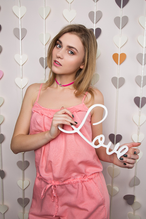 Beautiful sweet girl posing with love text Stock Photo