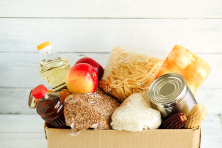 stock food at the isolation, the delivery of food in a crisis, food box on a white wooden background