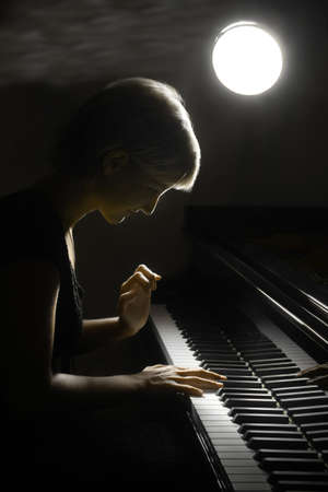Pianist musician piano music playing. Musical instrument grand piano with beautiful woman performer. photo