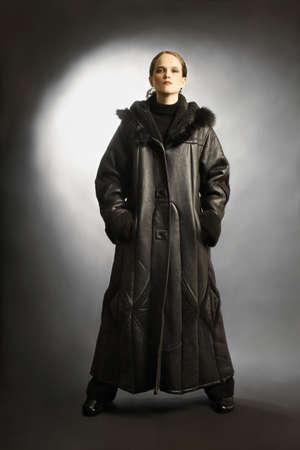 elegante: Manteau d'hiver en peau de mouton vêtements de mode sur la femme. Robe noire en peau de mouton-manteau avec capuche capuchon.