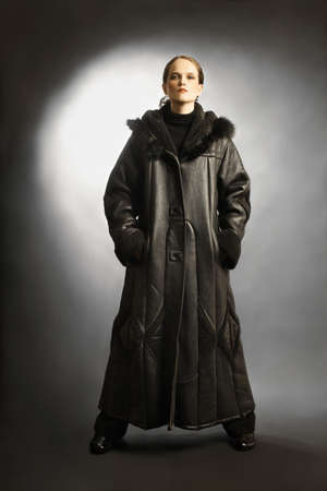 greatcoat: Sheepskin coat winter clothes fashion on woman. Black dress sheepskin-coat with hood cowl.