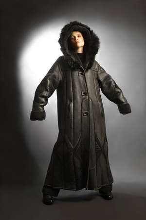 cowl: Sheepskin coat winter clothes fashion on woman. Black dress sheepskin-coat with hood cowl.