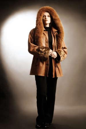 sheepskin: Mujer en el abrigo de moda de ropa de invierno. Chaqueta de cuero con capucha capucha.